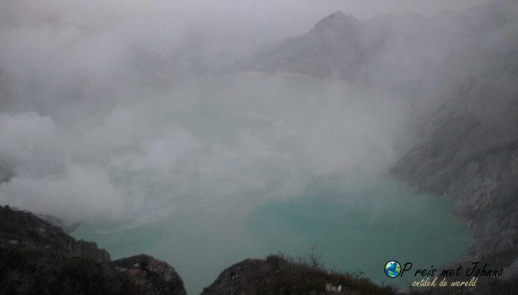 Uitzicht op het kratermeer van Kawah Ijen in de giftige wolken